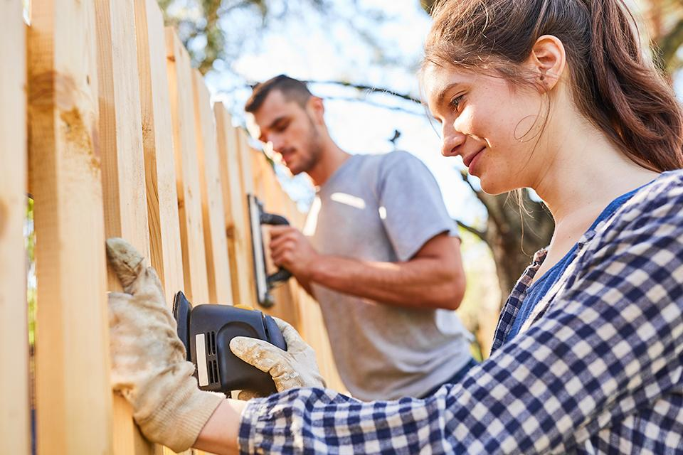 Man and woman sanding down a fence.