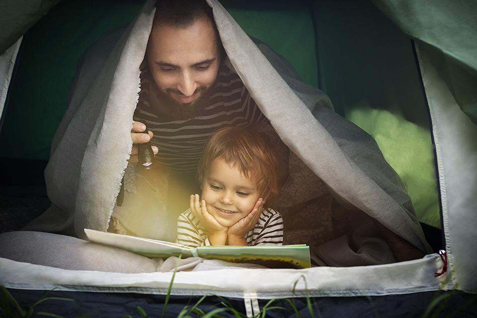 Father and son under blanket in a tent, reading a book together in torchlight.