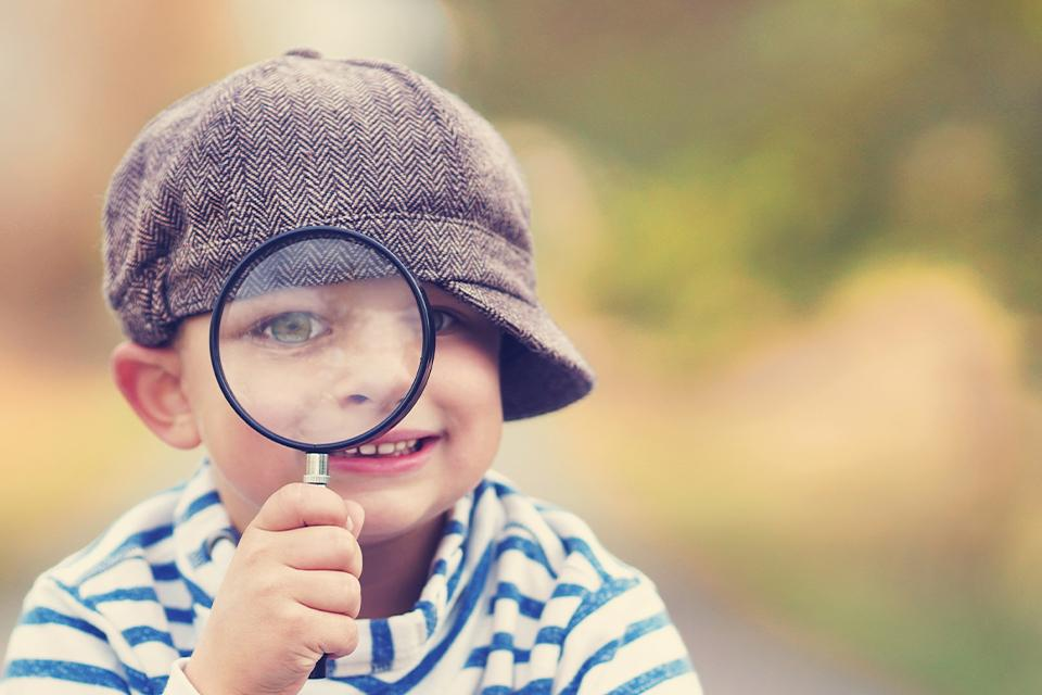 Young boy in blue & white striped top, wearing a grey hat with the peak to the side, looking through magnifying glass at the camera.