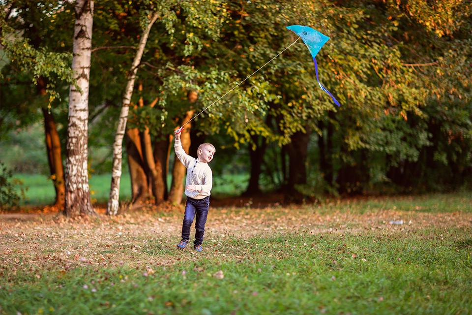 Young boy running outside with kite, with autumn trees in the background.