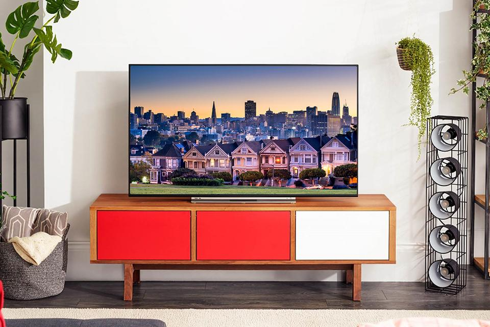 Toshiba Alexa TV on wooden TV stand.