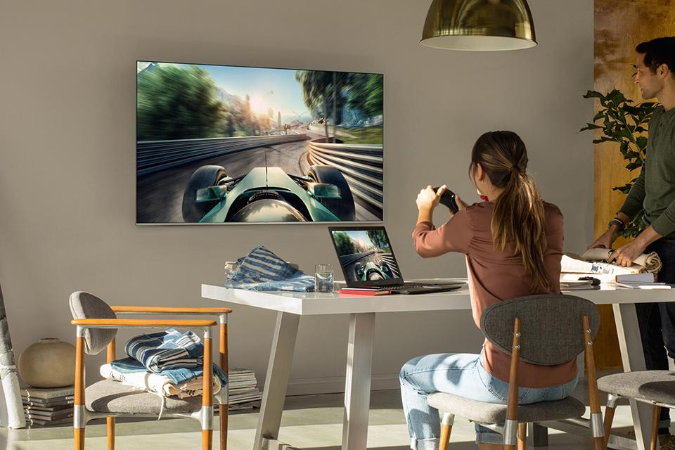 Woman playing a racing game on a smart TV.