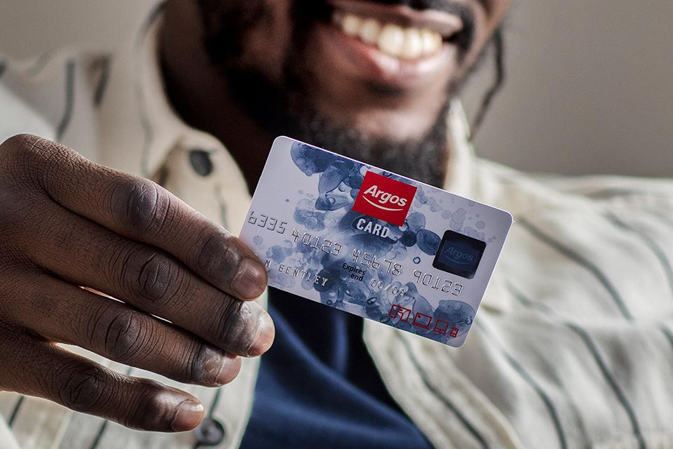 An image of a man smiling while holding his Argos Card.