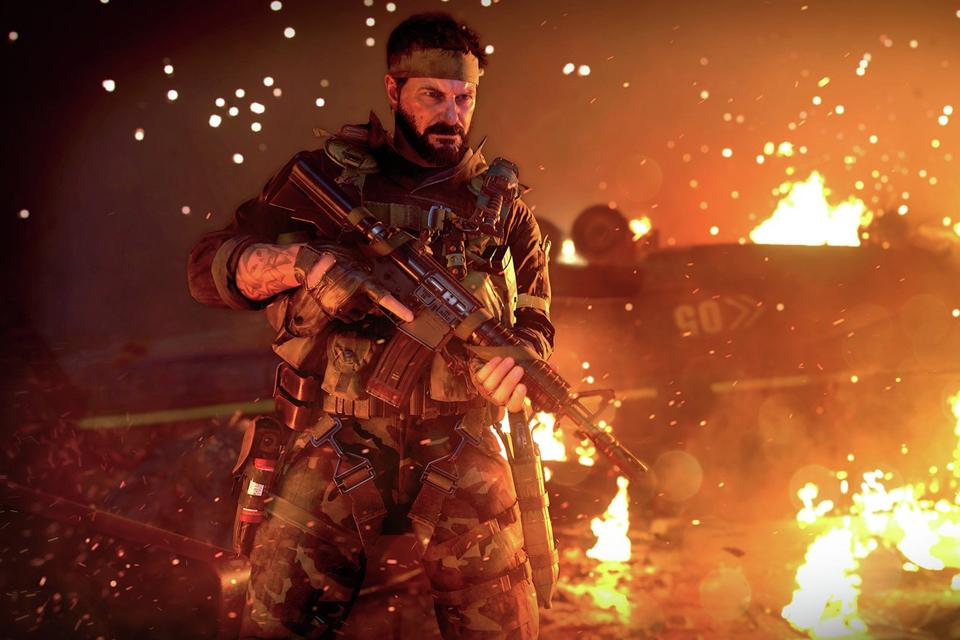 A screenshot from Call of Duty Black Ops Cold War showing a soldier in front of a burning vehicle.