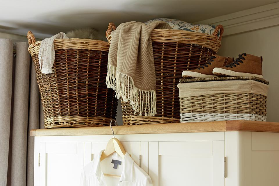 Storage baskets sitting on top of white wardrobe.