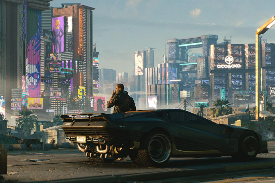 A screenshot from Cyberpunk 2077 showing a man leaning on a car against a neon-lit cityscape.