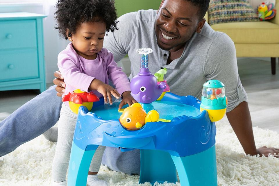 Dad and daughter playing with a children's activity table.
