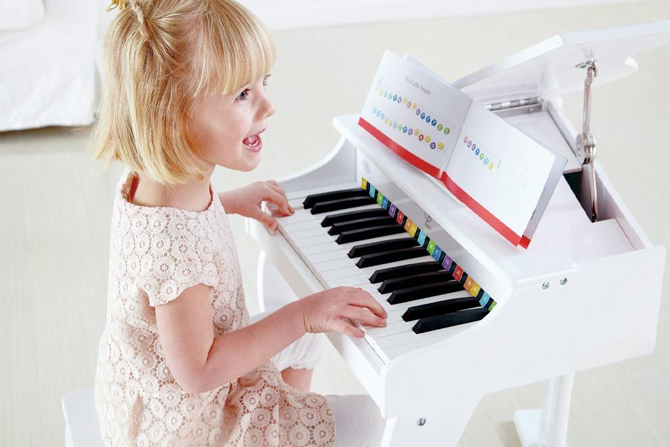 Girl sat at a mini white piano
