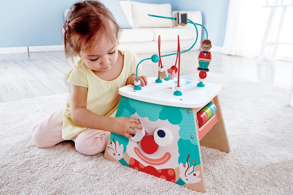 Girl playing with a wooden activity toy