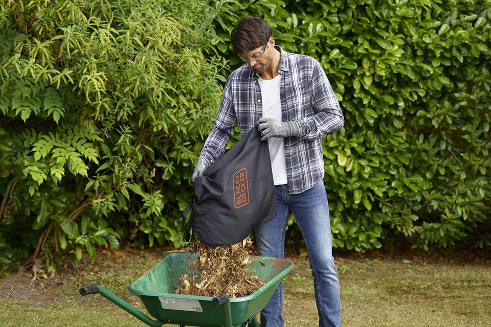 Man emptying a bag of leaves into wheelbarrow.