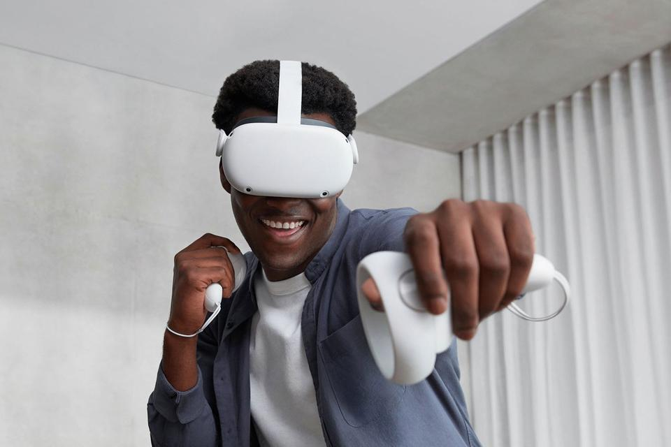 A man plays games using a Oculus visor and controllers.