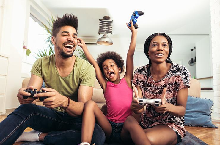 A child happily playing a video game with her parents.