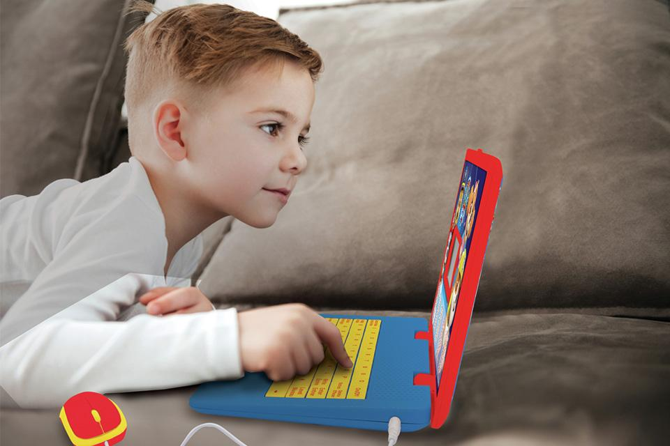 Boy playing on a toy laptop.