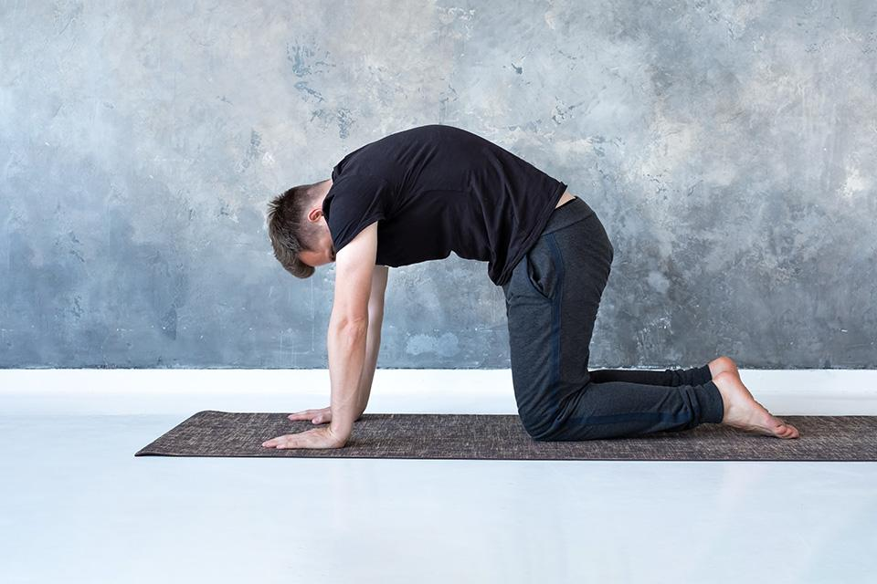 Man doing cat and cow pose on yoga mat.