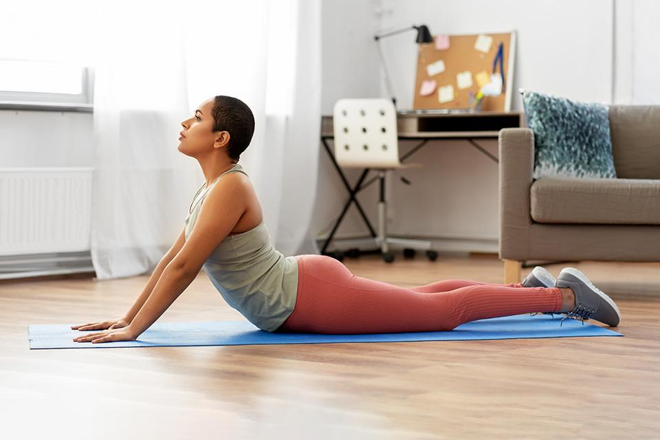 Woman doing cobra pose on yoga mat.