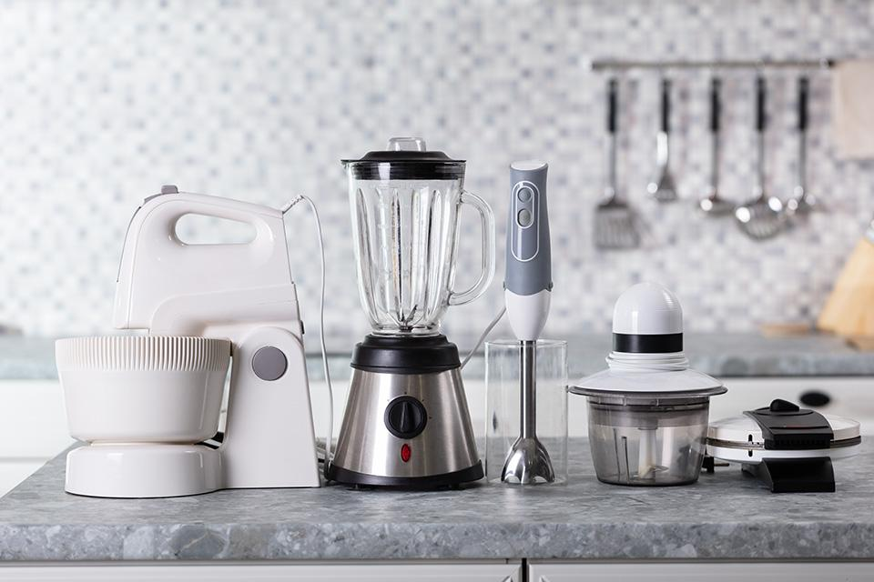 Small kitchen appliances lined up on counter top.