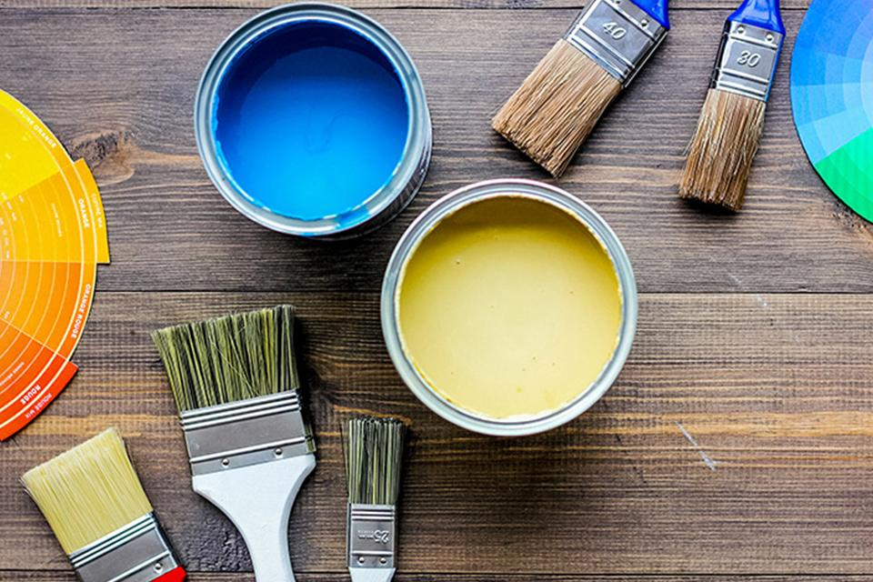 Tins of blue and yellow paint, paint brushes and colour wheels.