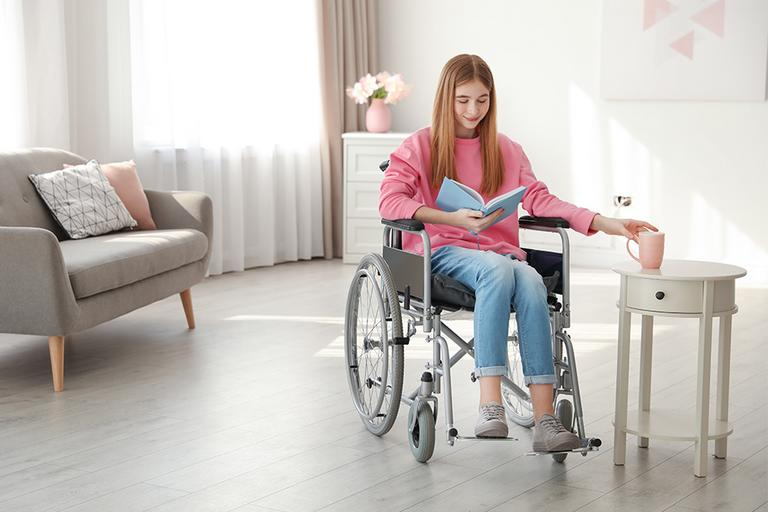 A girl in a wheelchair at home.