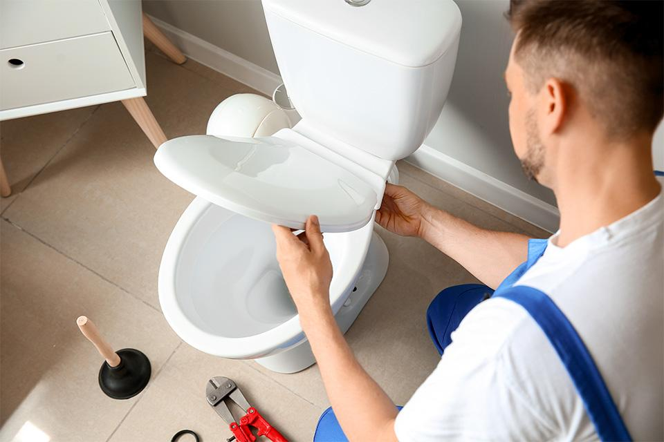 A man fitting a toilet seat.