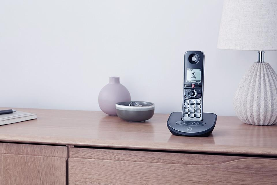 A BT cordless phone displayed in its recharge dock on a wooden table.