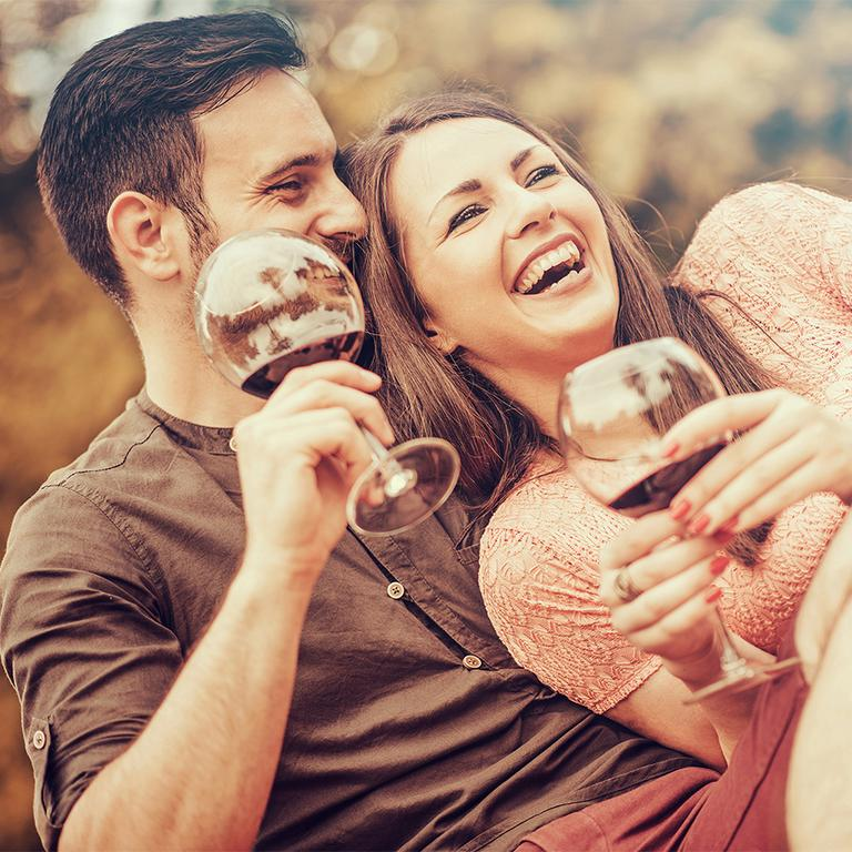 Man and woman laughing and holding wine glasses.