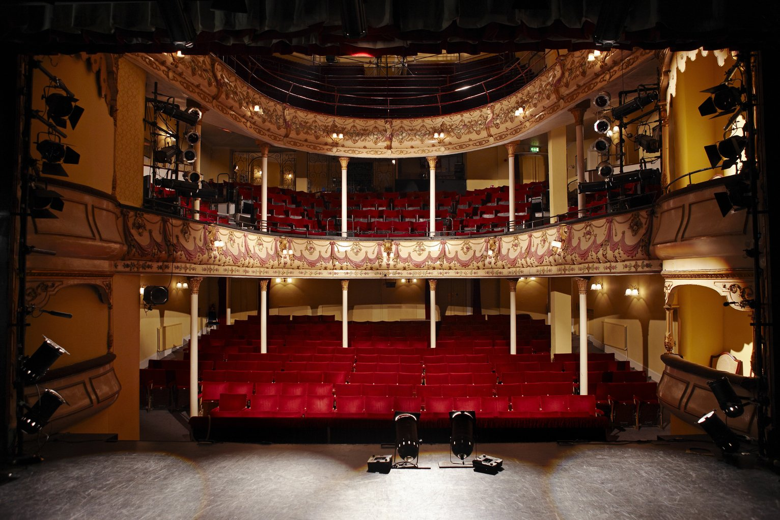 View of an empty theatre with red seats and balcony all hand.